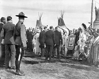 Nakoda (Stoney) - King George VI and Queen Elizabeth greet chieftains of the Stoney Indian Tribe, who have brought a photo of Queen Victoria, during the Royal Visit to Canada in 1939. The Treaties were originally signed by representatives of the British Crown acting in Queen Victoria's name.