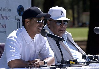 Deux hommes portant des lunettes de soleil. Le plus jeune d'entre eux sourit et parle dans un micro.
