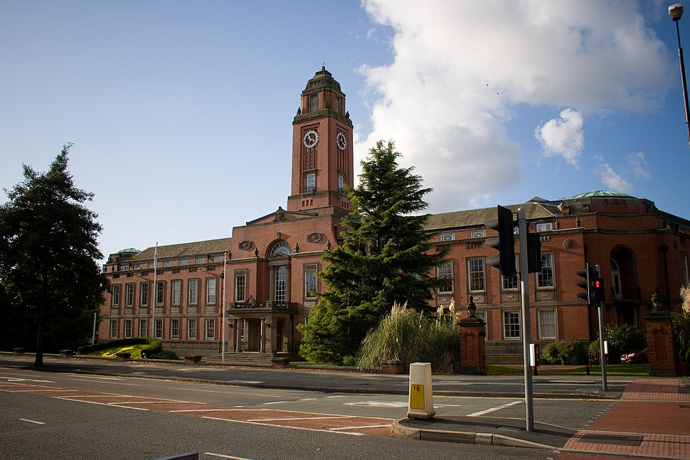 Red brick building with central square clock tower.