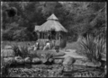 Two women seated on rocks in front of a thatched summer-house containing a drinking fountain at the Domain, Te Aroha, 1921 ATLIB 312054.png