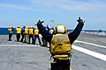 U.S. Navy Aviation Boatswain's Mate (Handling) 3rd Class Joshua Rabarabrokate, foreground, celebrates the launch of a Navy X-47B Unmanned Combat Air System demonstrator aircraft from the aircraft carrier USS 130514-N-TB177-579.jpg
