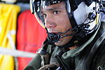 U.S. Navy Chief Naval Air Crewman Julio Grullon speaks through an internal communications system on an MH-60S Seahawk helicopter attached to Helicopter Sea Combat Squadron (HSC) 12 in the U.S. 7th Fleet area 140311-N-GR655-503.jpg