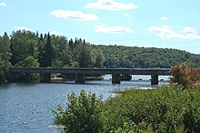 A river flowing between two banks covered in vegetation and trees. The river flows under a concrete bridge resting on four support piers into a lake in the background.