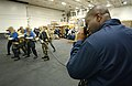 US Navy 030104-N-9964S-005 Photographer's Mate photographs sailors while they practice fighting an aircraft fire in the ship's hangar bay.jpg