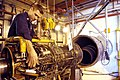 US Navy 030321-N-9693M-006 Aviation Machinist's Mate 2nd Class David Lyman, left, tightens a fitting on a T-64 turbo shaft engine for an MH-53E 'Sea Dragon' helicopter.jpg
