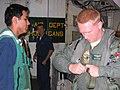 US Navy 050111-N-6974L-005 Aviation Electrician's Mate 3rd Class Eric Hernandez assists Lt. j.g. Nate Moore as he prepares for a daytime search and rescue (SAR) flight mission.jpg