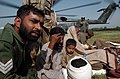 US Navy 051014-N-8796S-222 Pakistani Soldiers comfort injured civilians as they are moved to medical treatment from a U.S. Navy MH-53E Sea Stallion helicopter.jpg