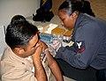 US Navy 060407-N-5291U-001 Fleet Surgical Team Five's (FST-5) Hospital Corpsman 3rd Class Tanisha M. Johnson administers a typhoid shot to a Sailor during a health awareness program held at Amphibious Group Three (AG-3).jpg