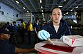 US Navy 060623-N-7526R-066 Airman Catherine Greninger drops a needle into a sharps container after taking blood from a USS Ronald Reagan (CVN 76) Sailor during a command post deployment health assessment.jpg