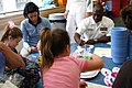 US Navy 070629-N-8110K-003 Chief Aviation Ordnanceman Rich Holmes, attached to the amphibious assault ship USS Wasp (LHD 1), displays his artistic abilities to some young patients during a Caps for Kids visit to the Jimmy Fund.jpg