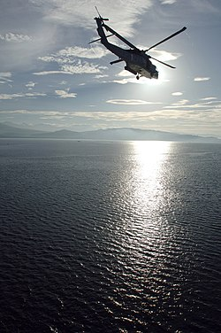 US Navy 080609-N-1450G-062 A MH-60S helicopter assigned to Helicopter Combat Squadron (HSC) 21, based out of San Diego, Calif., flies over Illana Bay, Philippines towards a Pacific Partnership medical civic action program.jpg