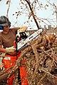 US Navy 080919-N-0193M-238 Hospital Corpsman Crystal Jackson cuts up a fallen tree.jpg