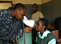 US Navy 100407-N-4657D-013 Hospital Corpsman 2nd Class Fitzroy Hall, an optometry technician assigned to a humanitarian civic assistance (HCA) medical team, examines a patient during an Africa Partnership Station West community.jpg