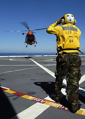 Airbus Group, Inc. - Landing signal enlisted Aviation Boatswain's Mate (Handling) 3rd Class Troy Palomino directs an H-65