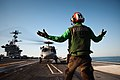 US Navy 101205-N-1783P-067 Airman Dequesne Noel, from Haiti, assigned to the Chargers of Helicopter Anti-Submarine Squadron (HS) 14, directs an SH.jpg