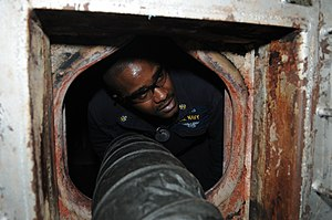US Navy 120121-N-SB587-032 Chief Machinist Mate Tyrelle Hines enters the fire box in the main machinery room of the amphibious assault ship USS Kea.jpg