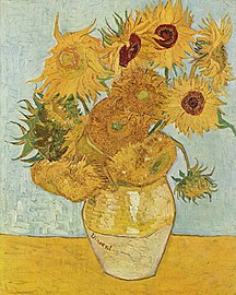 A ceramic vase with sunflowers on a yellow surface against a pale blue background.