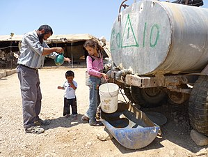 Water supply and sanitation in the Palestinian territories - Bedouins purchase water from water trucks in Khirbet A-Duqaiqah in the South Hebron Hills near the Green Line, a village with 300 residents that is not hooked up to water grid.