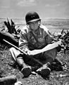 With the captured capital of Naha as a background, Marine Maj. Gen. Lemuel Shepherd, commanding general of the 6th Marine Division, relaxes on an Okinawan ridge long enough to consult a map of the terrain HD-SN-99-02889.jpg