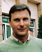 An out-of-focus portrait shot of a dark-haired man in a lime-green v-neck sweater.