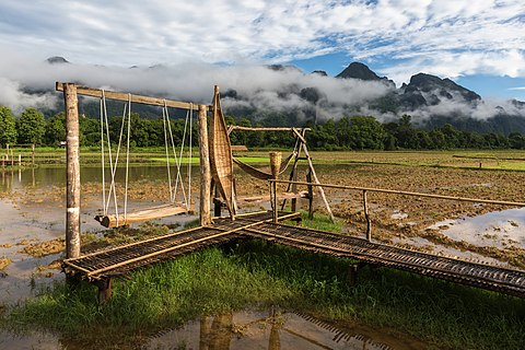 Wooden bench swing and wicker hammocks on a bamboo footbridge in paddy fields a sunny day during the monsoon, Vang Vieng, Laos