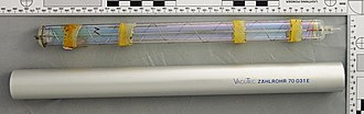 Geiger–Müller tube - Thin-walled glass G–M tube showing a spiral wire cathode. The tape bands are for fixing compensating rings