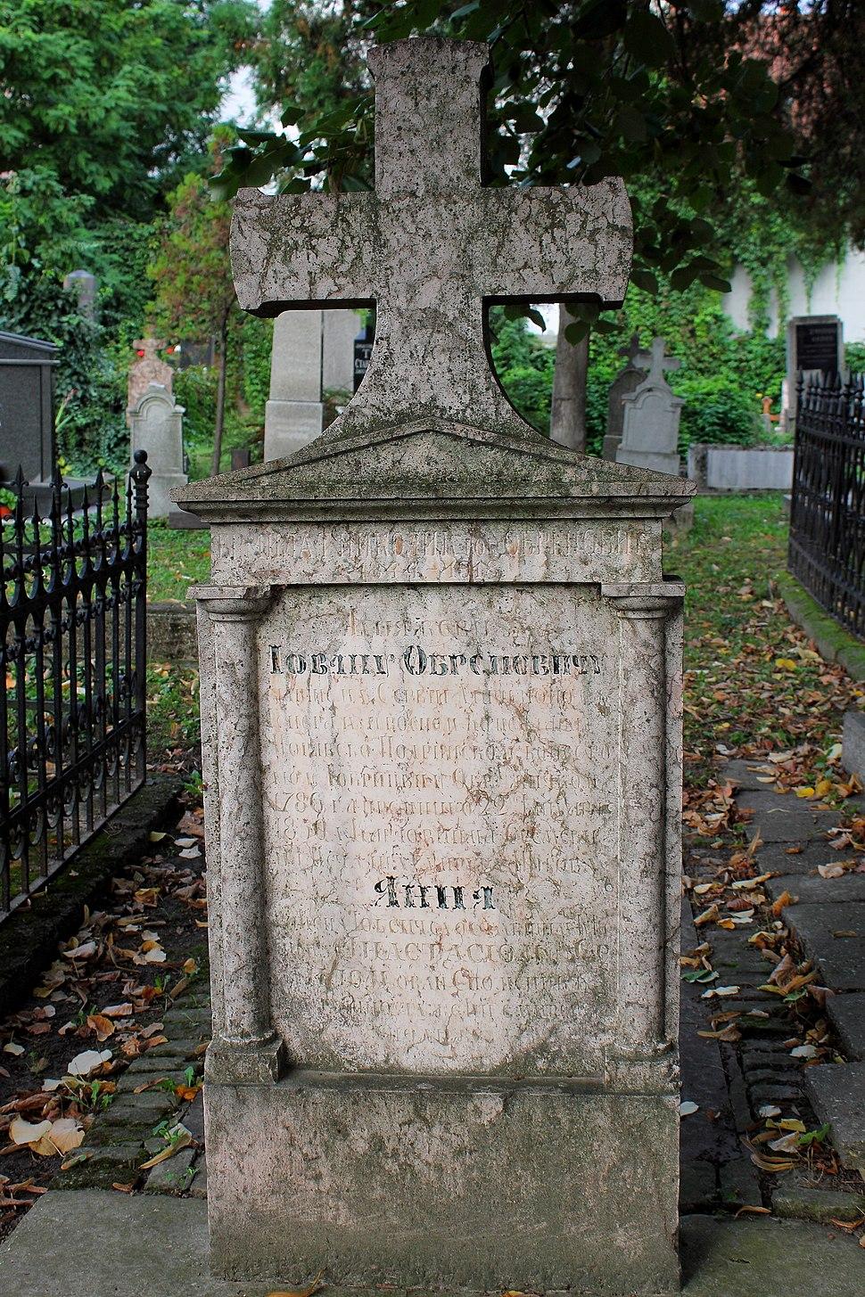 Стари споменик од ружичастог камена са крстом Јована Обреновића
