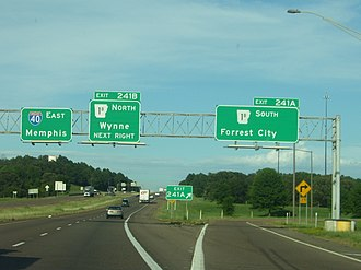 Gore (road) - The two diverging white lines at front mark the theoretical gore of this highway exit, while the physical gore is the grass area that starts immediately after it