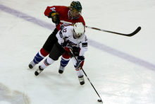 A female ice hockey player, wearing white, is playing the puck as an opposing player, wearing red, is directly behind her trying to hit her.