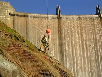 Englebright Dam - A miner scaling the rock face below the dam during installation of the Narrows II Powerhouse Flow Bypass System in 2006
