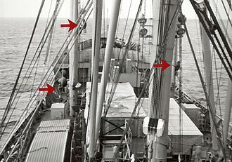 Deck department - The ship's bosun, an able seaman (AB) day worker, and a watchstander AB are seen here working aloft aboard a U.S. freighter to maintain cargo rigging.