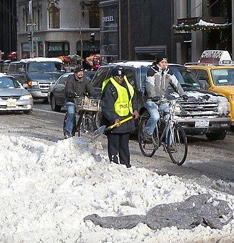 Cold-weather biking - Cold-weather cylists riding in the rightmost part of the lane in New York City.