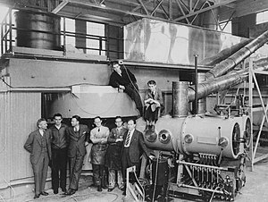 Six men in suits and ties stand stand in front of gigantic machinery. Two more are sitting in top of it.