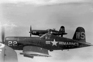 A propeller-driven fighter aircraft in level flight, with the word 'Marines' written on the side