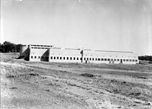 Black and white photograph of large building in the middle of an open grassed area