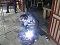 A fabricator welds metal plates together.jpg