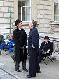 Actors in period costume sharing a joke whilst waiting between takes during location filming.