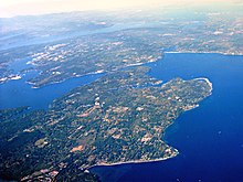 Aerial view of the northern part of Bainbridge Island adjoining Puget Sound, with Agate Passage in center.