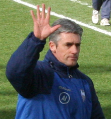 A man on a sports field waving