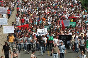 """2012 Republic of Macedonia inter-ethnic violence - Albanian protesters holding various signs, including signs reading """"I am Muslim I am not a terrorist,"""" and green or black flags bearing the shahada, an Islamic declaration of faith."""