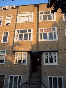 A four story, brick apartment block showing the building's facade, with several windows and an internal staircase leading into the block.