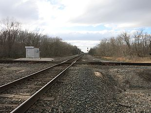 Photo shows two single-track railroads crossing at a 90-degree angle.