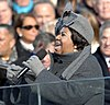 A woman her mouth open, holding a microphone. She is wearing a gray hat with a large bow, gray gloves, and a gray jacket. In the background is a crowd of people.