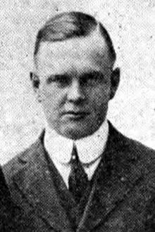 Head and shoulders of white middle aged man in 1920s suit and tie