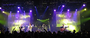 Four-man rock group performing on stage, spotlit, with row of darkened fans in the foreground