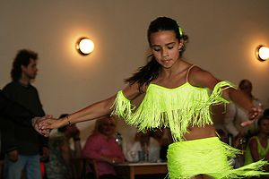 A young girl dancing Cha-cha-cha. The girl mov...