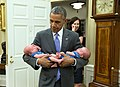 Barack Obama carries the twin boys of Katie Beirne Fallon, Director of Legislative Affairs.jpg