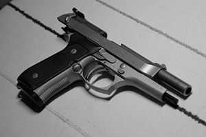 Beretta 92 - A Beretta 92FS Inox with the slide retracted, showing the exposed ejection port and barrel mechanism.