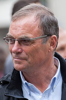 Color photograph of Hinault, looking to the left, wearing glasses