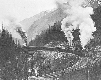 """Big Hill - Looking west, 1890. Safety Switch No. 1 and its uphill spur are shown foreground and right; the truss bridge under the rear of the train, now known as the """"Old Bridge"""", survives as a tourist attraction"""